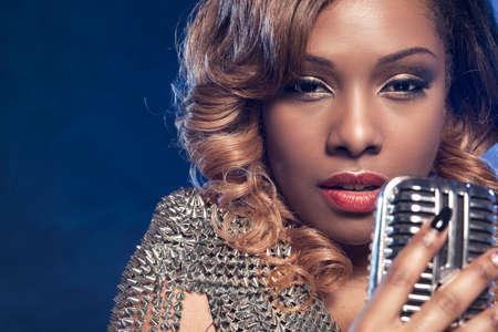 gente cantando: Hermosa mujer africana que canta con el micrófono Foto de archivo