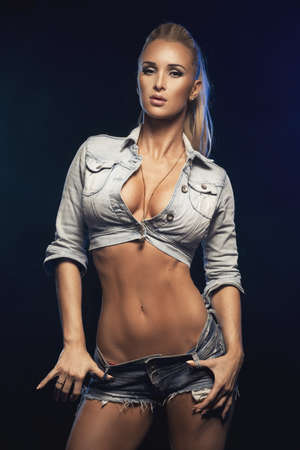 Fashionable blonde beautiful woman posing in studio wearing short jeans, looking at camera. Stock Photo