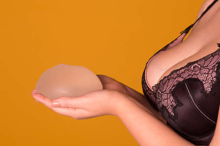 women breast: Silicone implants on hand and natural brest