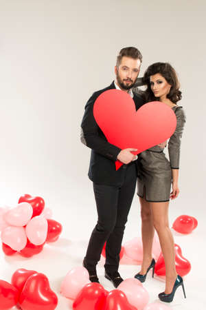 sexy dress: young smiling caucasian couple holding sign in form of red heart