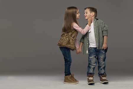 A portrait of a laughing girl and a smiling boy. Autumn style Foto de archivo