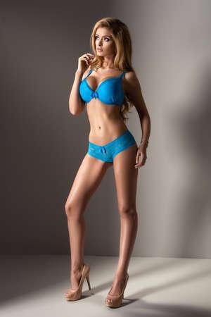 jungen unterwäsche: Attraktive blonde Frau posiert in Unterwäsche auf grauem Hintergrund