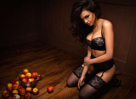 Sexy beautiful girl sitting on a floor with apple Фото со стока