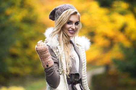 winter fashion: Young girl smiling in autumn scenery