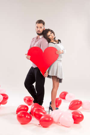 embracing couple: young smiling caucasian couple holding sign in form of red heart