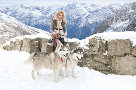 snow forest: Happy young woman playing with siberian husky dogs in winter forest Stock Photo