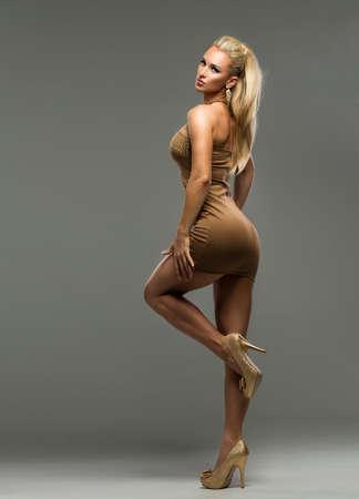 Sexy blond lady in dress on dark background