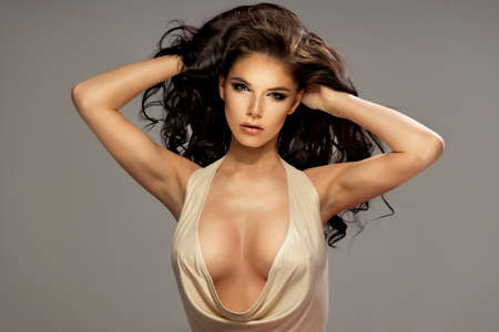 female breast: Portrait of beautiful sensual brunette woman with long curly hair. Beauty photo.