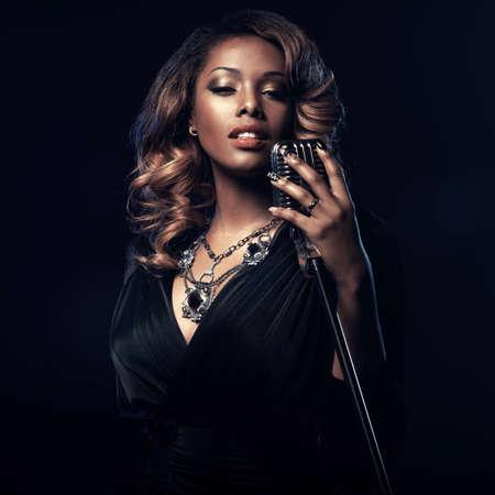 musico: Hermosa mujer africana que canta con el micrófono Foto de archivo