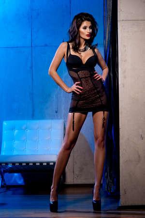 tacones: mujer sensual vistiendo traje ropa interior negro y tacones altos, de pie