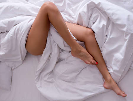 legs  white: Woman legs on the bed in white bedclothes