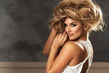 beaux seins: Portrait de la belle femme blonde sensuelle avec de longs cheveux bouclés. Photo de beauté.