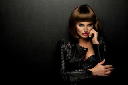 Sexy brunette vrouw in leren jas Stockfoto