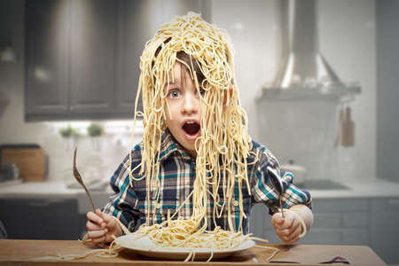 boy sitting: Surprised boy with pasta on the head Stock Photo