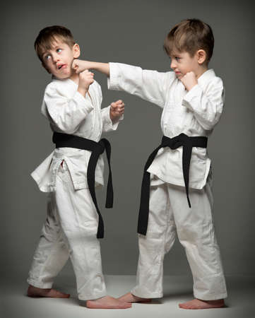 judo: Little boys in uniform practicing judo. The same person two times