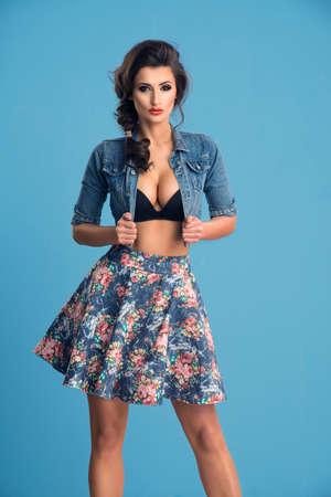 Fashionable sensual brunette woman posing on blue background