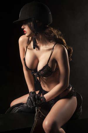 femme noire nue: Corps de femme sexy avec une selle et un casque comme jockey Banque d'images