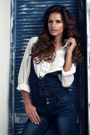 femme brune sexy: Sexy femme brune en chemise blanche et jeans Banque d'images
