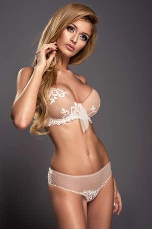 nudo integrale: Donna bionda sexy che propone in biancheria nudo, guardando a porte chiuse.