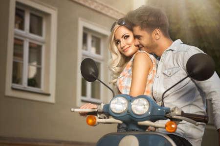 стиль жизни: Счастливая пара свободного свободы вождения скутера на сегодняшний день летнего