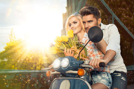 romantic hug: Happy free freedom couple driving scooter on summer date