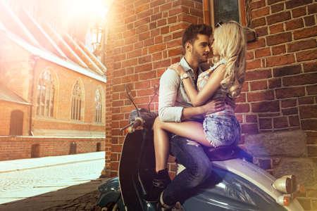 embracing couple: Feliz libertad libre par de conducci�n scooter sobre la fecha de verano Foto de archivo