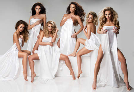 女性のグループは、スタジオで白い生地のみを着用します。