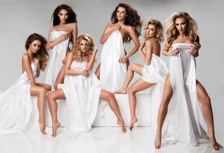 nudo integrale: Gruppo di donna indossare solo materiale bianco in studio