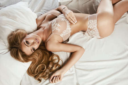 Photo of sexual blond woman lying  in bed. Perfect fitness body. Stock Photo