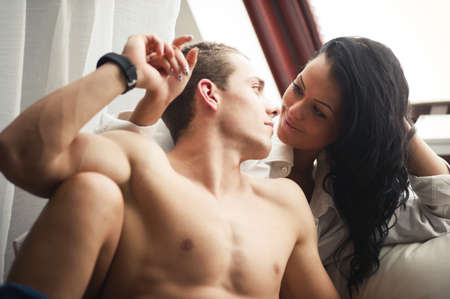 parejas sensuales: Pareja feliz en el sofá en la mañana Foto de archivo