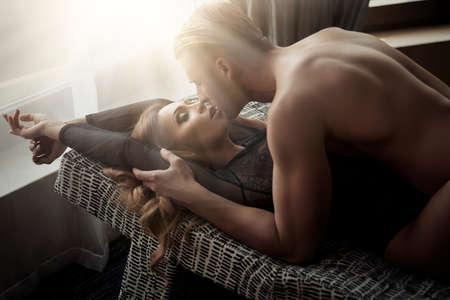 sexo pareja joven: Pareja bes�ndose joven atractiva y jugando en la cama.