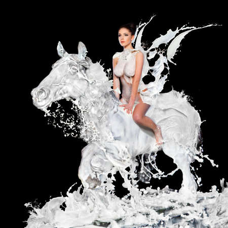 body milk: Sexy woman with milk sitting on horse Stock Photo