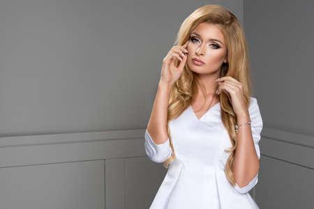 beautiful blonde woman: Blond beauty wearing white dress