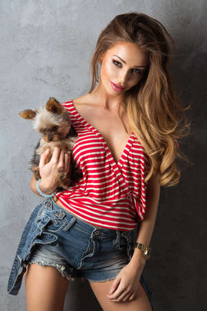 erotic dress: Beautiful girl in jeans shorts and a white - red shirt with dog