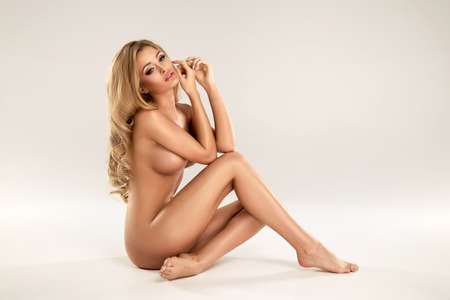 sexy nude girl: Beautiful young naked blonde woman sitting over the background Stock Photo