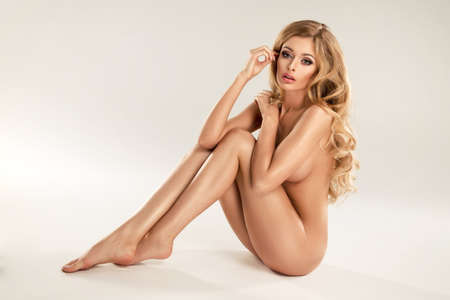 topless brunette: Beautiful young naked blonde woman sitting over the background Stock Photo