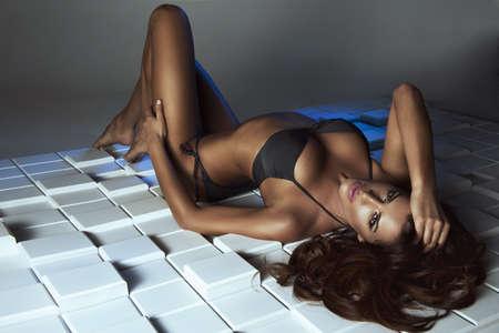 pechos: Mujer atractiva del encanto con el pelo oscuro en lencer�a negro tumbado en el suelo. Fondo blanco y azul de los bloques de madera de forma regular