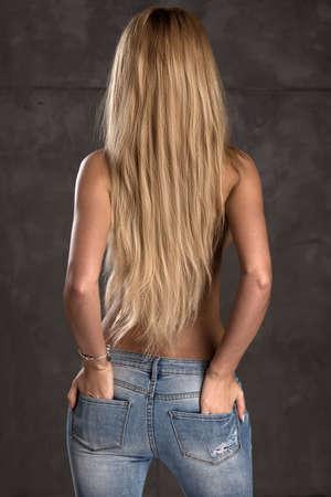 ジーンズだけでストレート ブロンドの髪を持つ若い女性の後ろ側