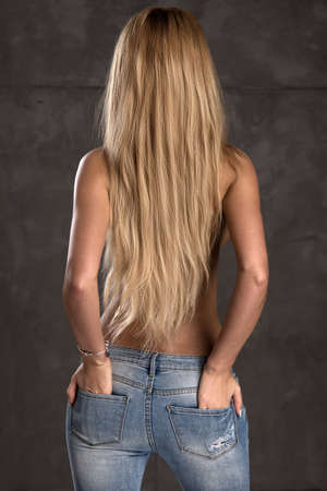 Back side of young woman with straight blonde hair only in jeans Stockfoto