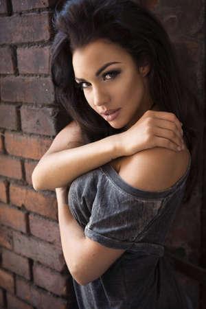 mujer sexy desnuda: Mujer morena sensual que presenta en la pared de ladrillo Foto de archivo