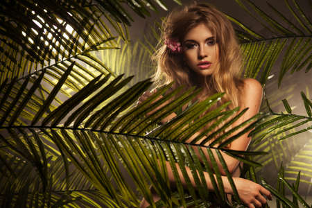 flores exoticas: Sexy belleza rubia joven en un bosque tropical