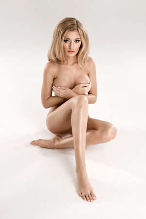 nude breasts: Beautiful young naked blonde woman sitting over the background Stock Photo