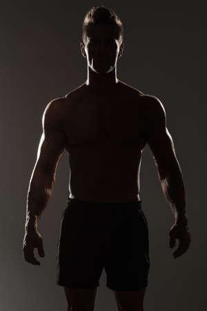 modelos desnudas: Silueta de un hombre muscular en la sombra Foto de archivo