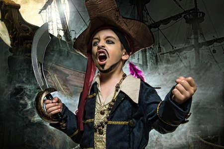 Eine böse Junge trägt einen Piraten-Kostüm. Er steht auf dem Hintergrund des Schiffes