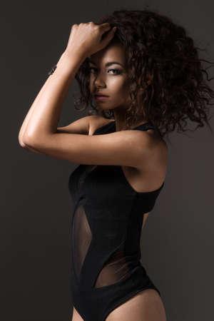 femme noire nue: Afro femme sexy posant en lingerie noir, regardant la caméra.