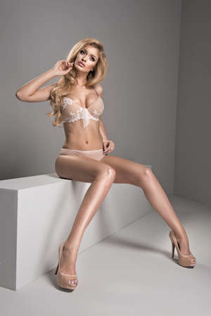 glamour nude: Blonde sexy woman posing in nude lingerie, looking at camera. Stock Photo