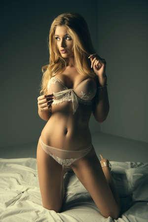 mujer rubia desnuda: Foto de la mujer rubia sexual en la cama. Cuerpo físico perfecto.