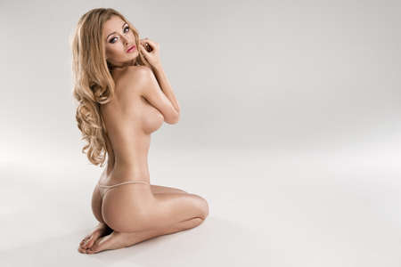 nudo integrale: Bella giovane donna bionda nuda seduta su sfondo