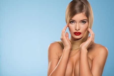 Nude blonde woman: Retrato de la mujer atractiva joven con labios rojos, sobre fondo azul Foto de archivo