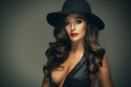 Sexy attractive brunette woman with black hat in studio